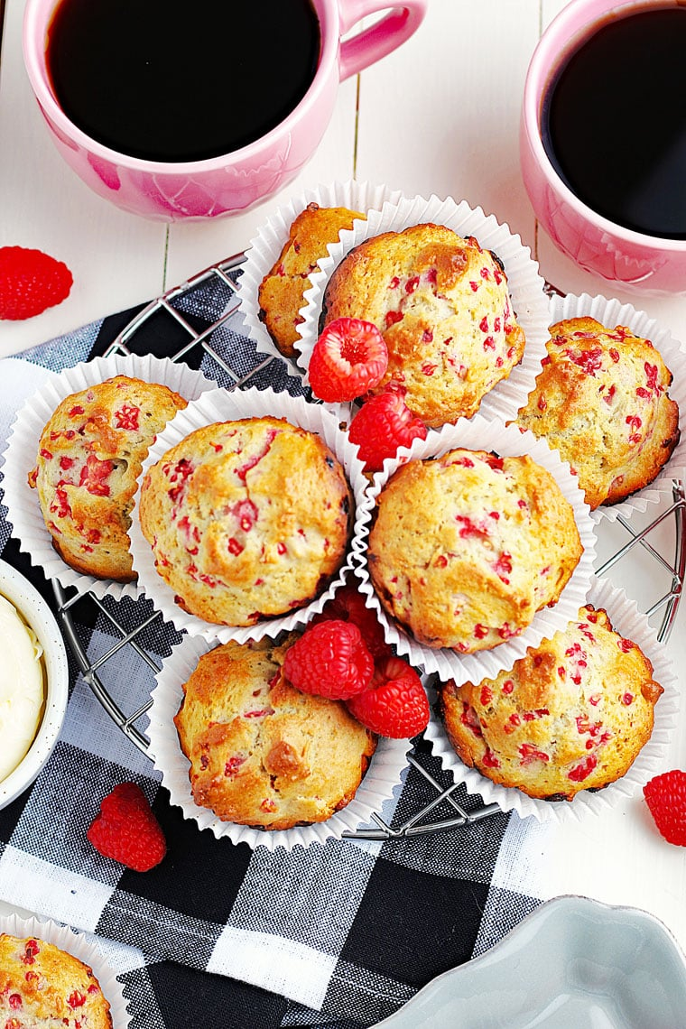 Overhead shot of a bunch of raspberry muffins in white paper liners on a wire rack on a black and white napkin with mugs of coffee.