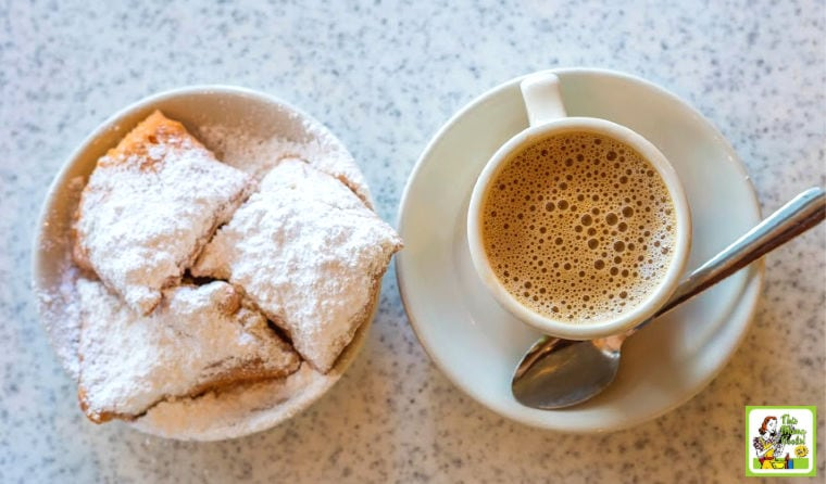 French style donuts also called beignets topped with powdered sugar next to a cup of frothy coffee.