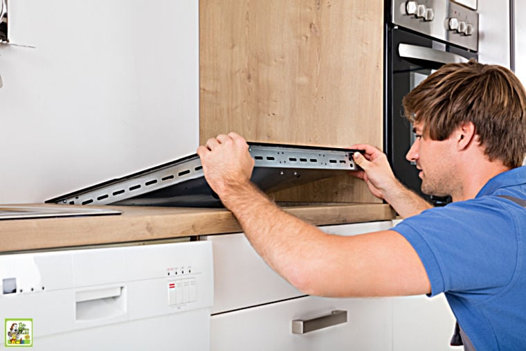Man in blue shirt installing an induction stove in a kitchen counter.