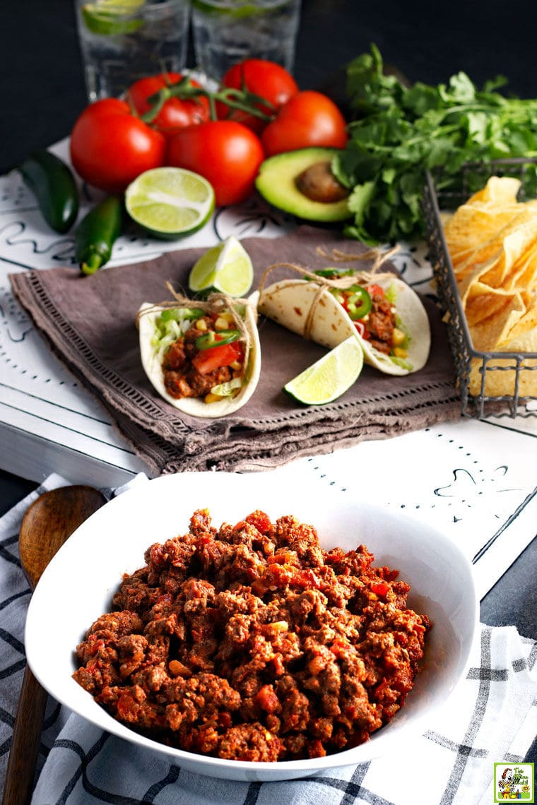 A white dish of spicy Crockpot Taco Meat with tacos, limes, tortilla chips, tomatoes, chilis, and cilantro.