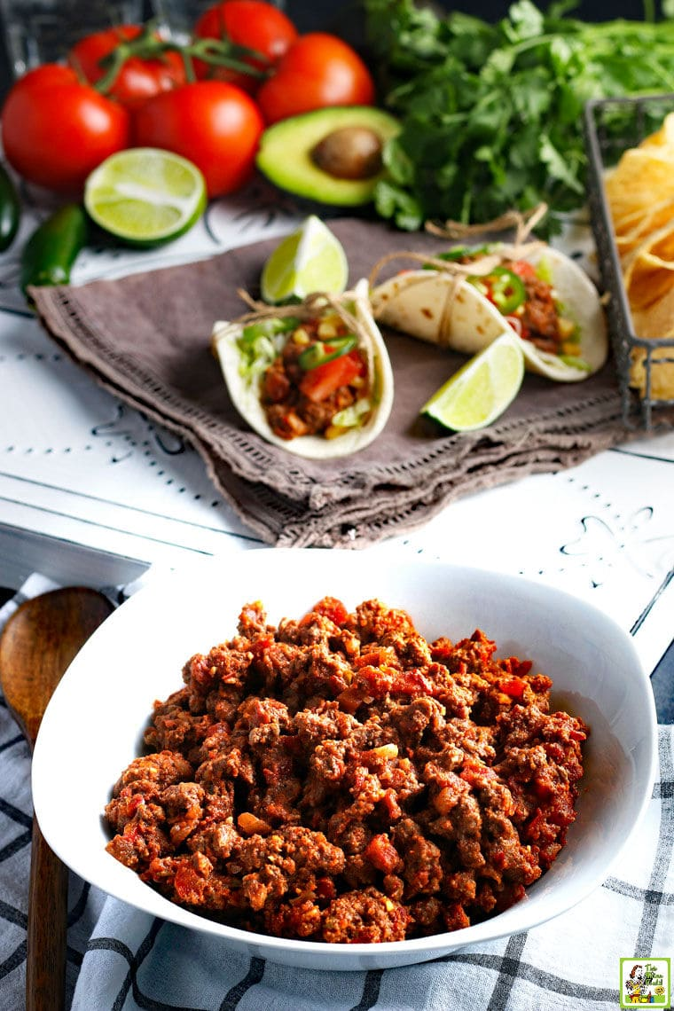 A white bowl of Crockpot Taco Meat with slow cooker tacos, limes, tomatoes, and avocados.