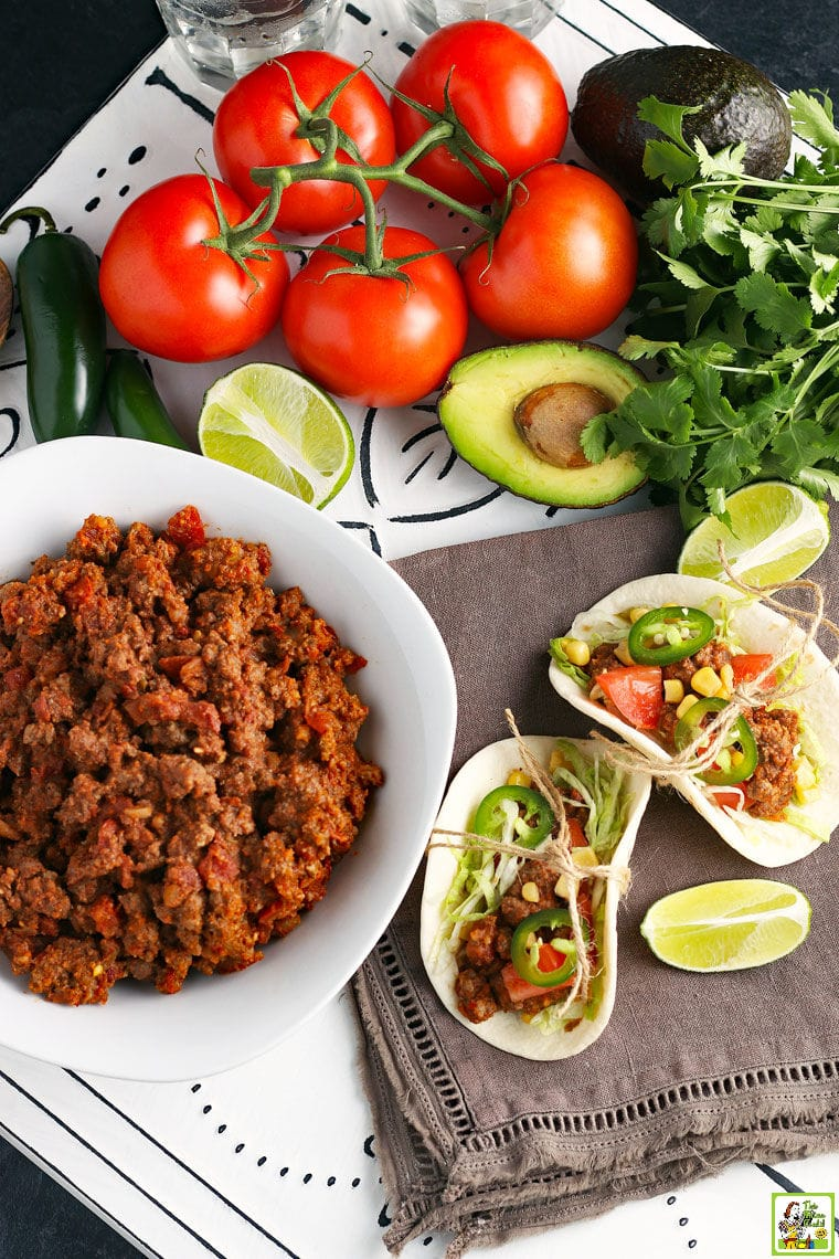 A bowl of cooked Crockpot Taco Meat with crock pot tacos, limes, tomatoes, and avocados