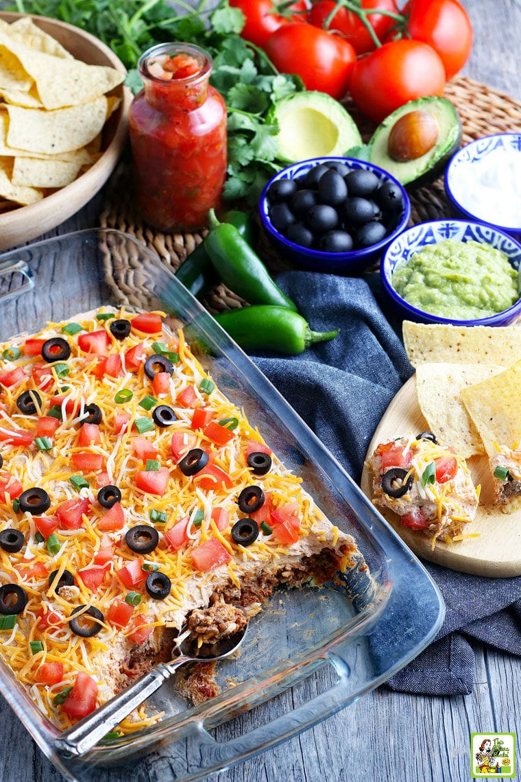 A casserole dish of taco dip with cheese, olives, tomatoes, and green onions layered with sour cream, refried beans and ground beef.
