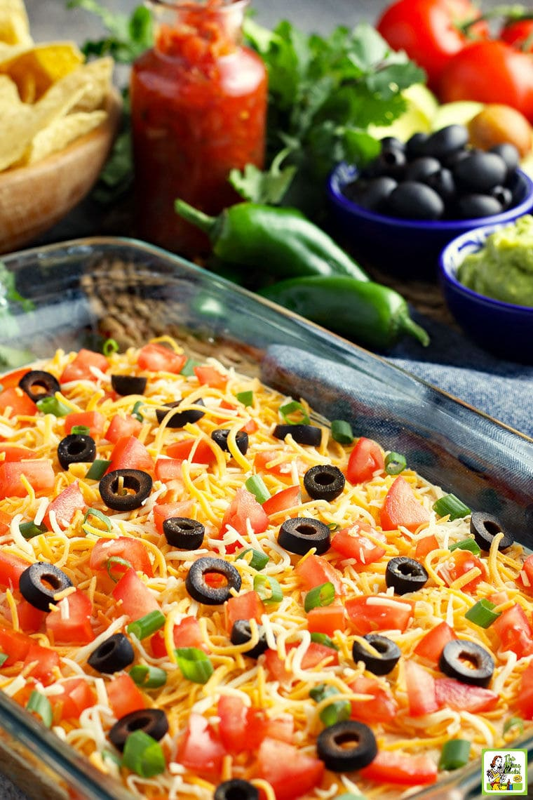A casserole dish of layered taco dip with cheese, olives, tomatoes, and green onions. With olives, chiles, and tomatoes in the background.