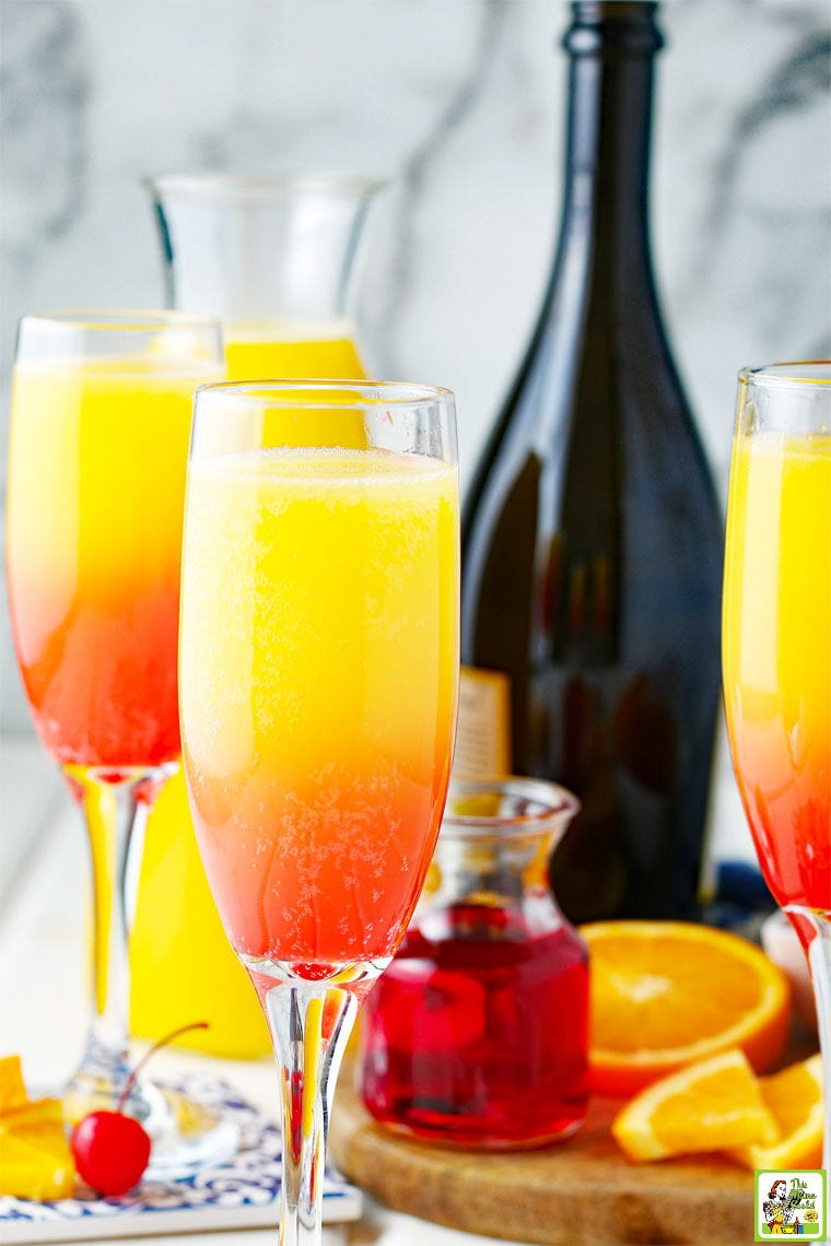 Sunrise Prosecco Mimosas served in fluter champagne glasses. With a bottle of sparkling wine in the background.