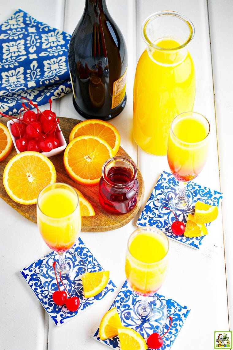 Prosecco Mimosas in champagne glasses, garnished with maraschino cherries and orange slices.