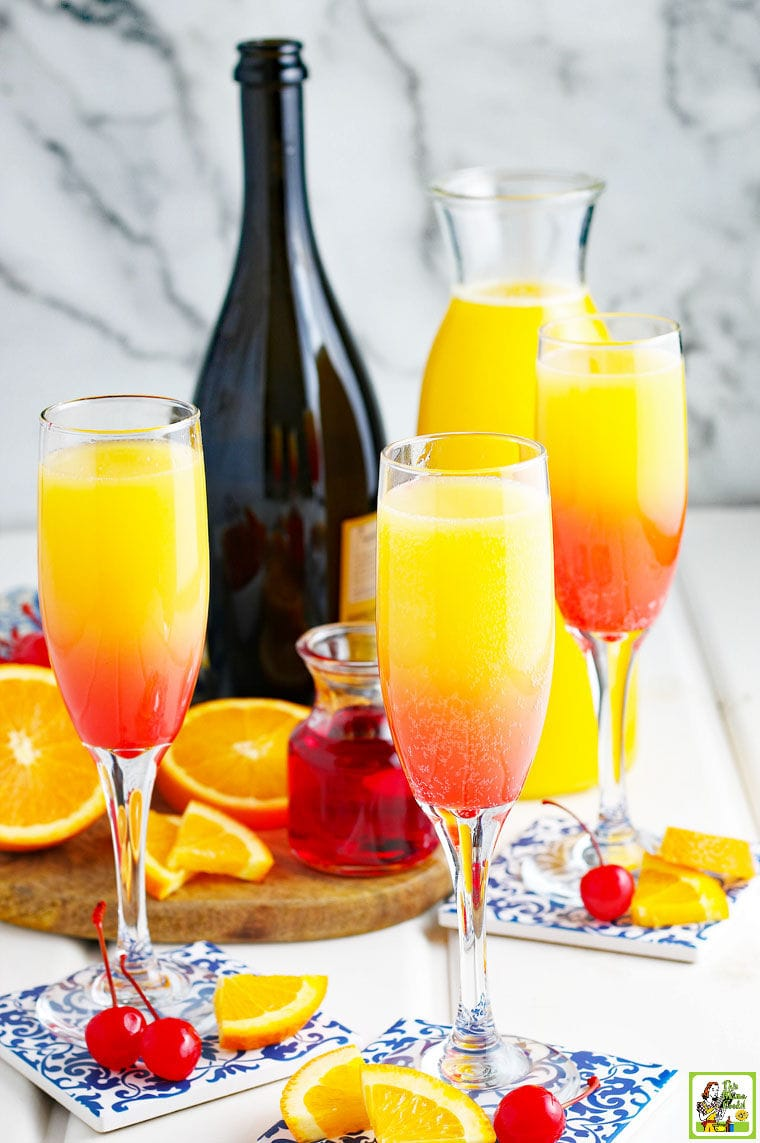 Prosecco Mimosas in champagne glasses with grenadine syrup, garnish of maraschino cherries and orange slices, and a bottle of sparkling wine.