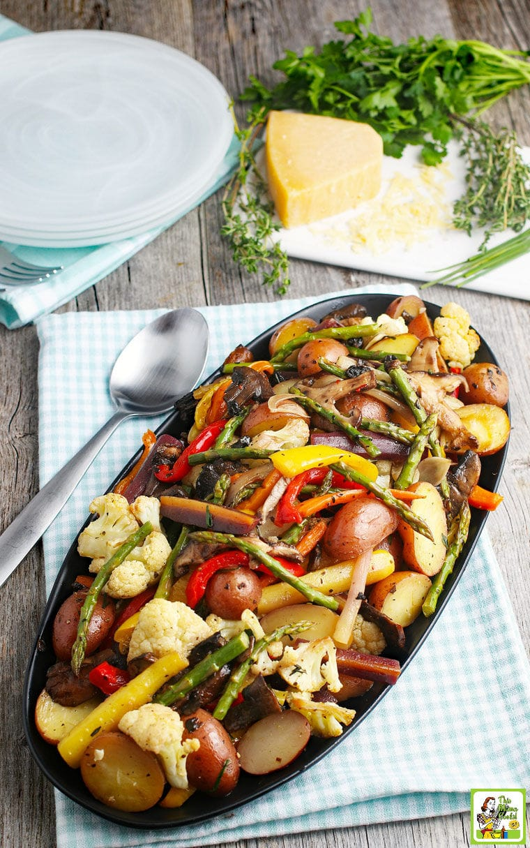 A platter of oven roasted veggies like potatoes, asparagus, cauliflower, and bell peppers placed on a napkin with a spoon, with herbs and cheese in the background.