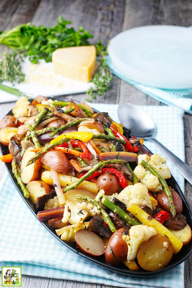 A platter of oven roasted veggies like potatoes, asparagus, cauliflower, and bell peppers.