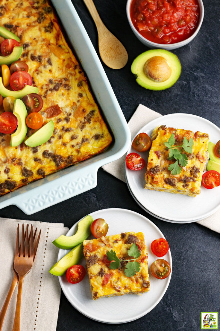 White plates a cheesy breakfast casserole with a large baking dish. Served with tomatoes and avocados.