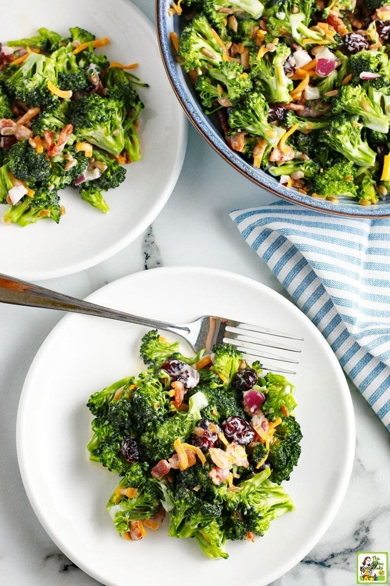 Broccoli Bacon Salad on white plates and in a blue bowl with blue and white napkin