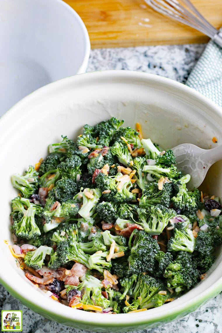 White bowl of Broccoli Bacon Salad with red onions and shredded cheddar cheese.