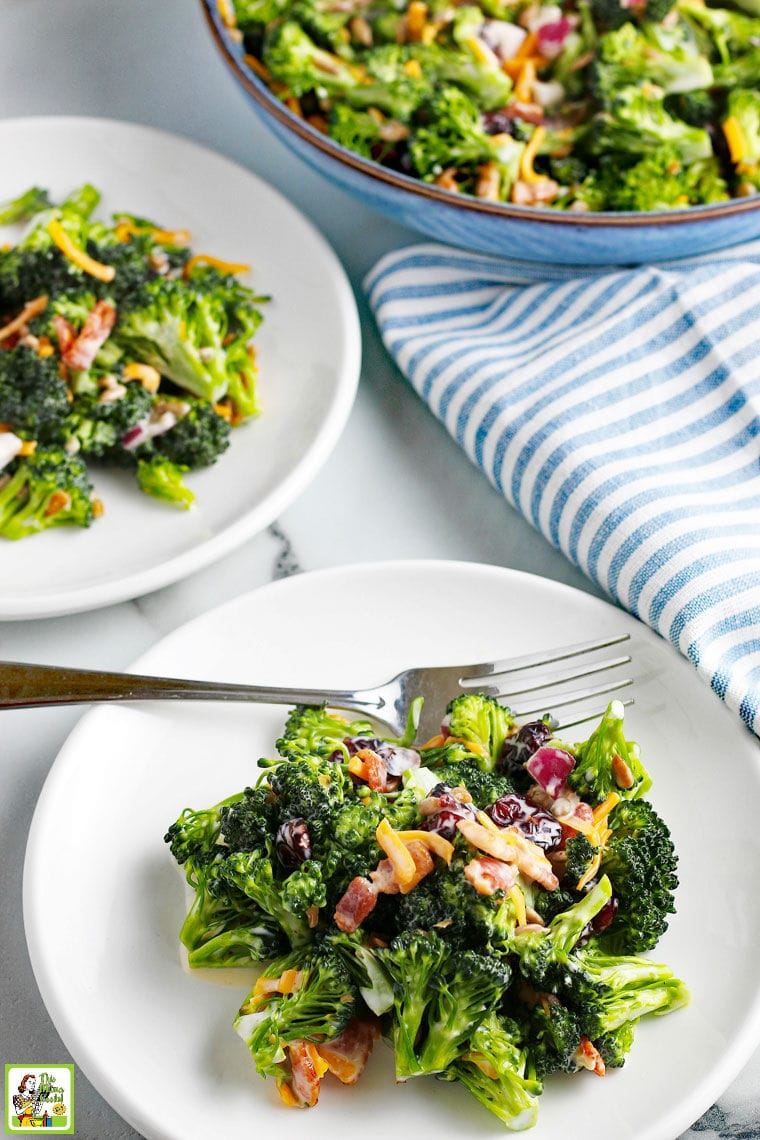 Broccoli Salad with cheese, onion and cranberries on white plates with forks and blue and white napkins. With a blue salad bowl in the background.
