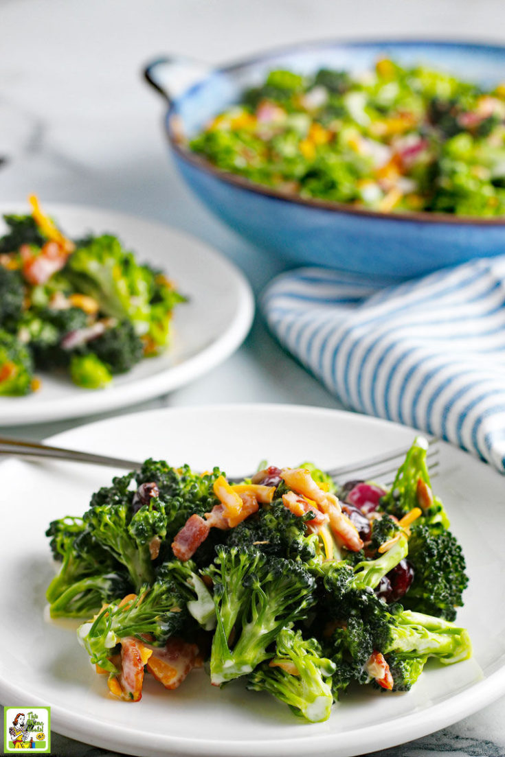 Two whites plates of Broccoli Salad with cheese, red onion, sunflower seeds, and cranberries. Blue and white napkins and a blue salad bowl in the background.