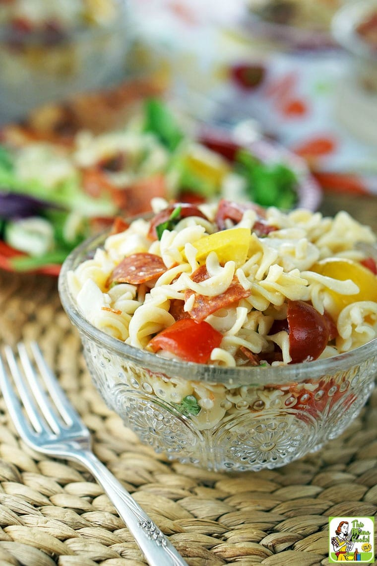 A glass bowl of Caprese Pasta Salad with fork.