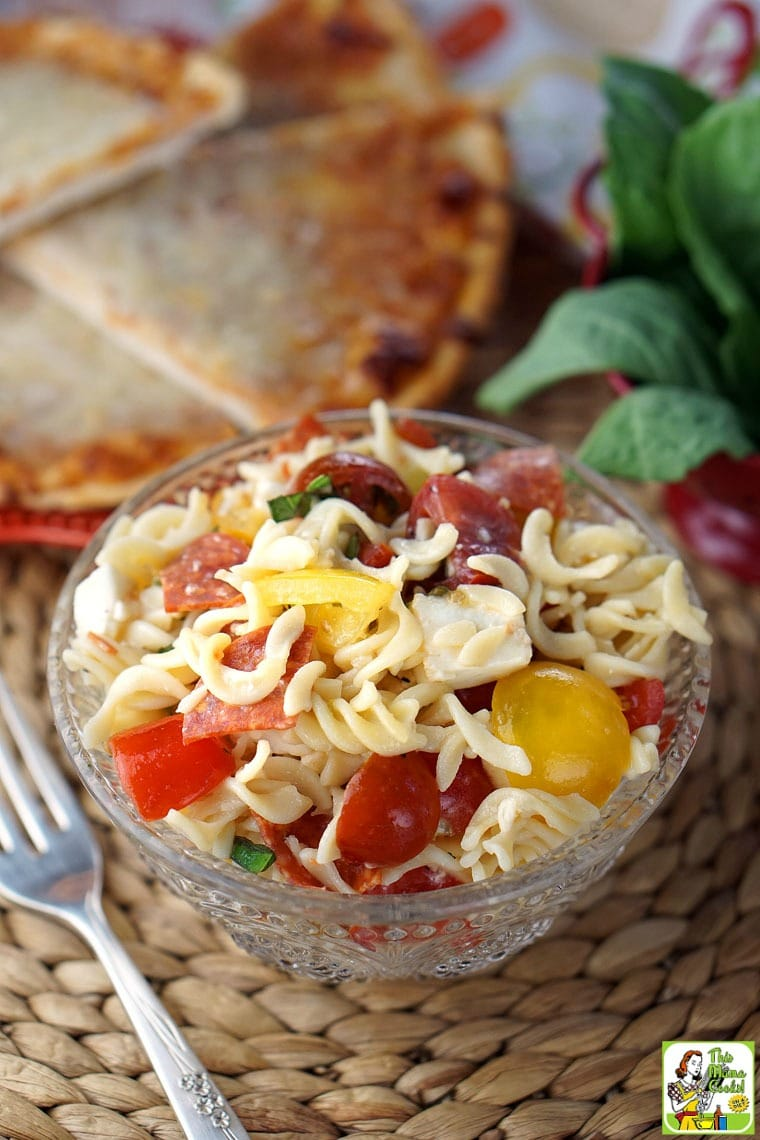 A glass bowl of Caprese Pasta Salad with fork with slices of pizza in the background.