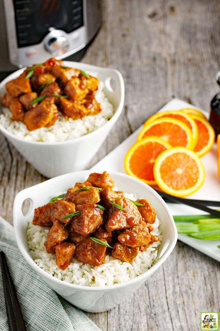 Two bowls of Instant Pot Orange Chicken on white rice.
