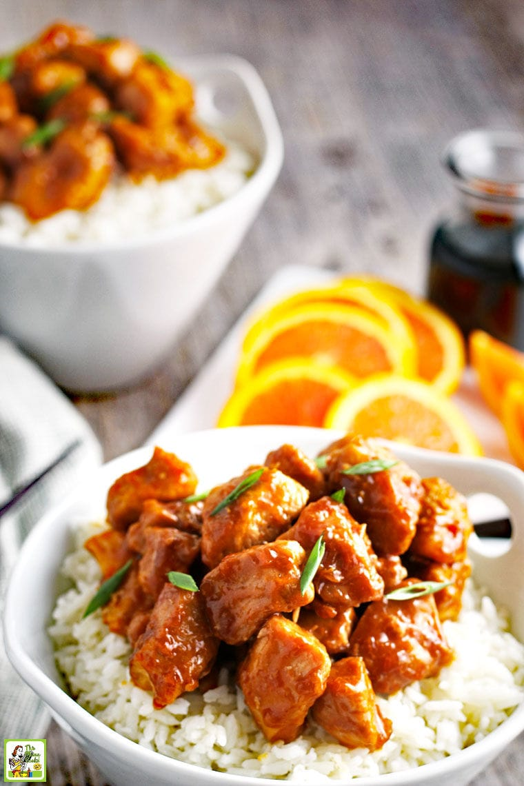A white bowl of Orange Chicken on white rice with slices of oranges.