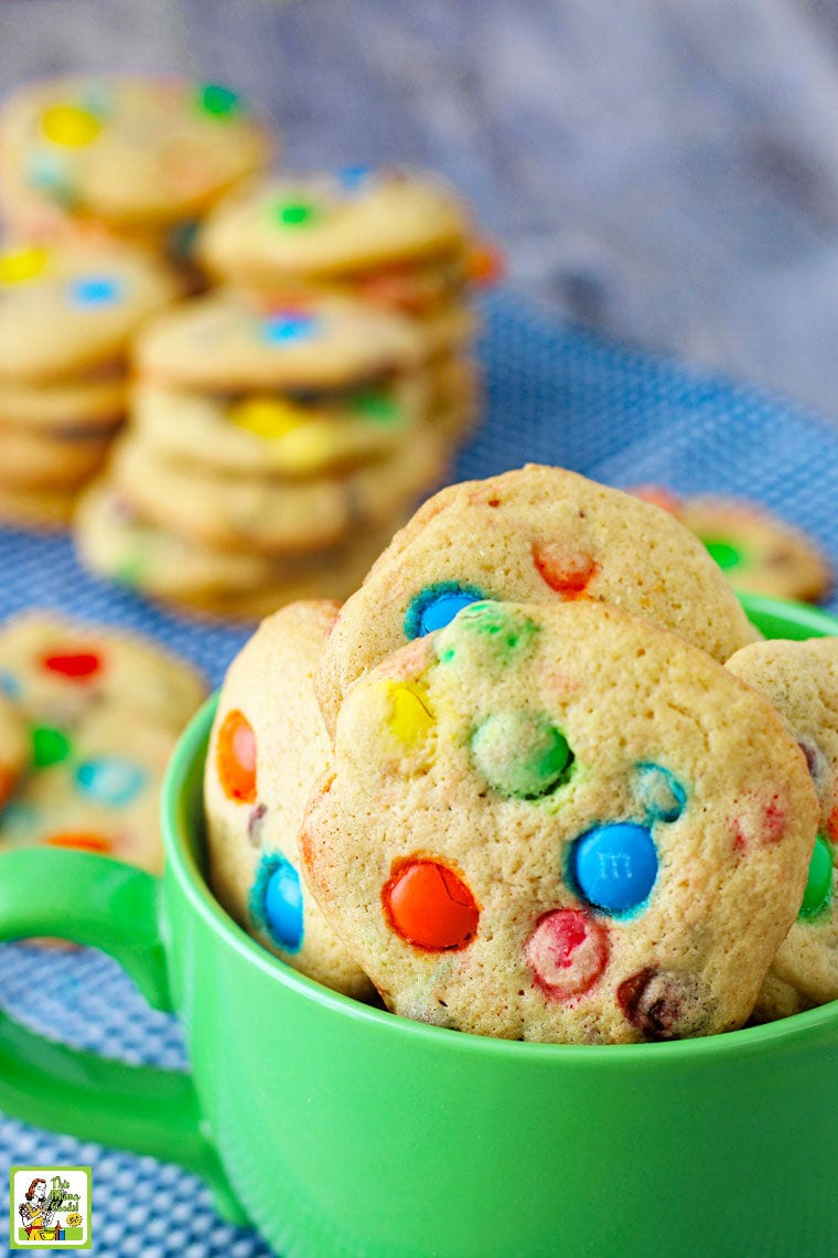 Closeup of a green mug filled with M&M Chocolate Chip Cookies