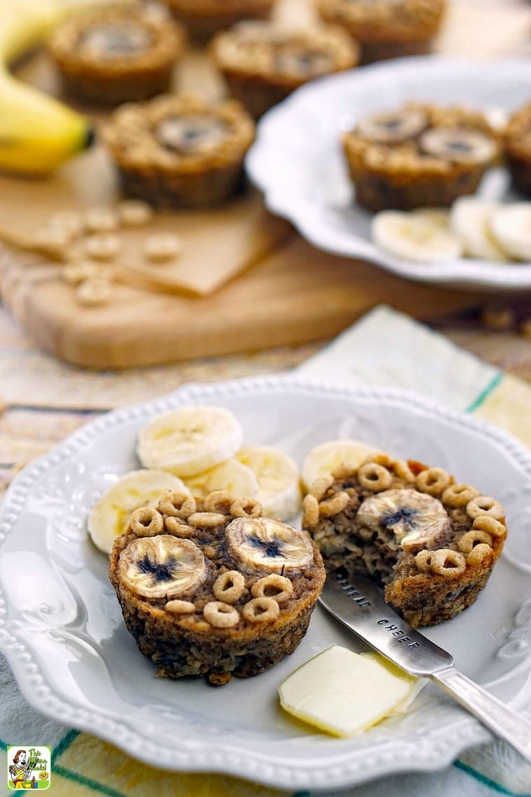 Two gluten free banana muffins on a white plate with slices of banana and butter pats.