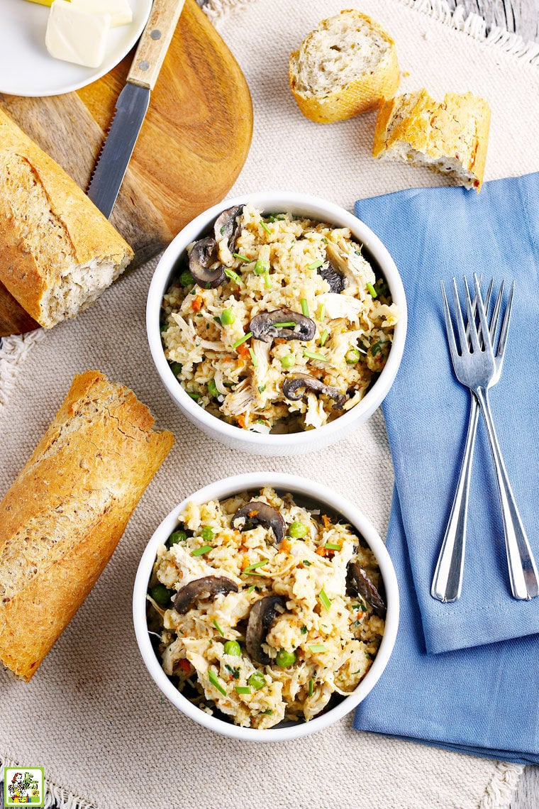 Two white bowls of Instant Pot Chicken and Rice with bread, blue napkins, and forks