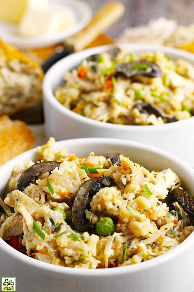 Closeup of bowls of chicken and rice with peas, carrots and mushrooms