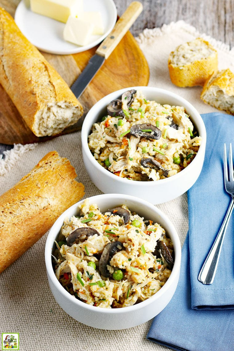 Bowls of Chicken and Rice with a blue napkin, forks, and French bread