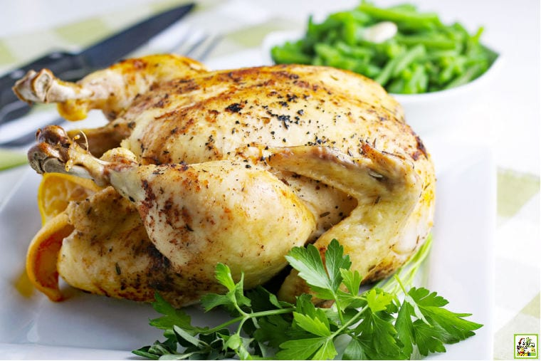 An Instant Pot Whole Chicken on a white platter with fresh herbs with a bowl of green beans in the background.