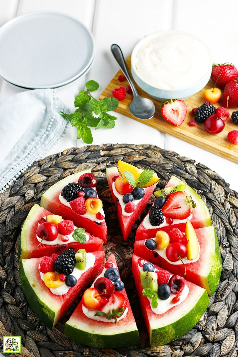 A Watermelon Pizza with cream cheese frosting, fruit and plates