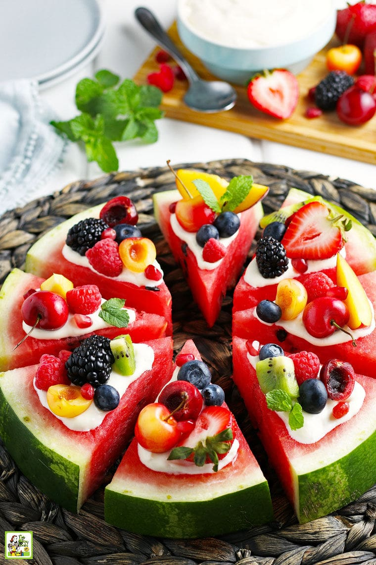 Slices of watermelon pizza with fruit and mint on a woven straw mat on a white tablecloth