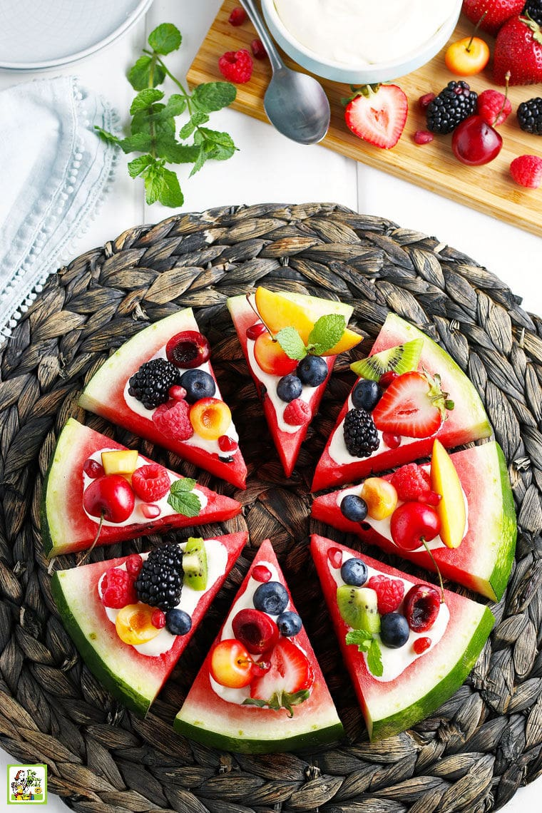 Slices of watermelon pizza with slices of fruit and berrieson a woven straw mat on a white tablecloth