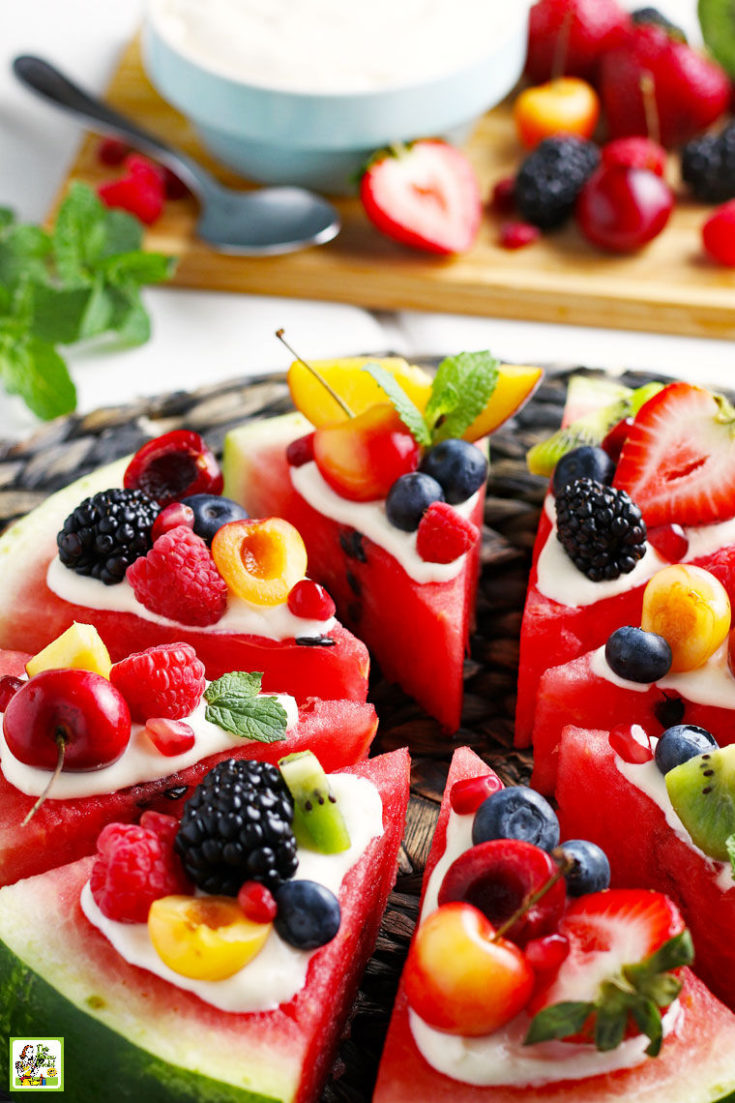 Closeup of slices of watermelon pizza with fruit and berrieson a woven straw mat with more fruit in the background