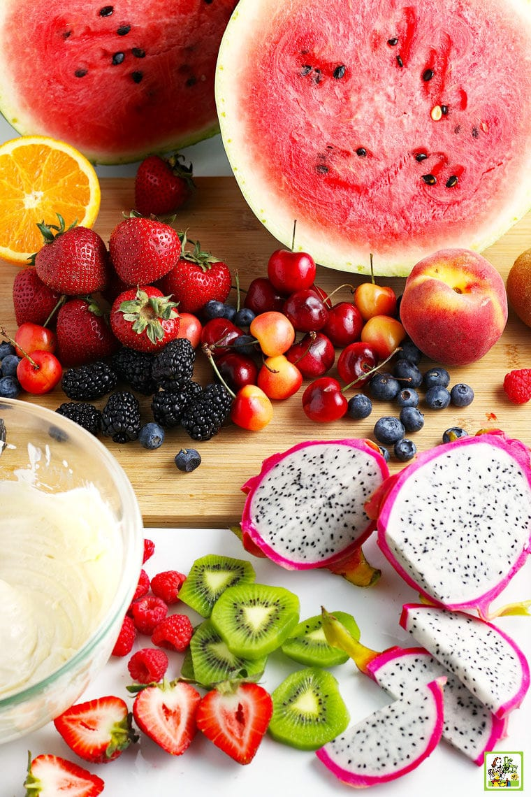 Fruit, berries, sliced fruit and a bowl of cream cheese frosting for Watermelon Pizza