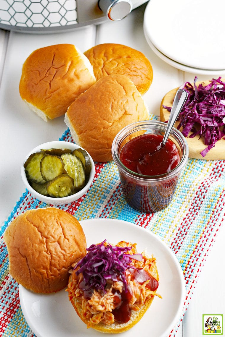 BBQ Chicken Sandwiches with red cabbage, a pot of BBQ sauce, buns, and pickles