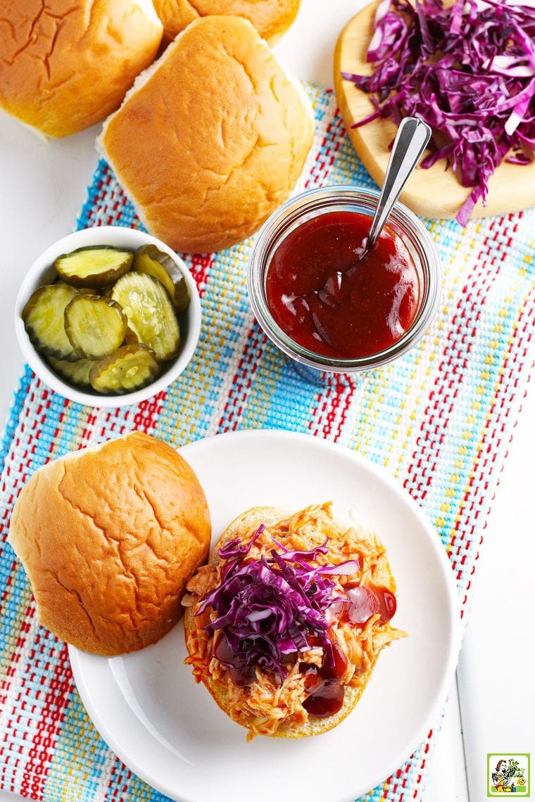 Overhead shot of BBQ chicken sandwiches, pickles, BBQ sauce, and buns on a striped tea towel