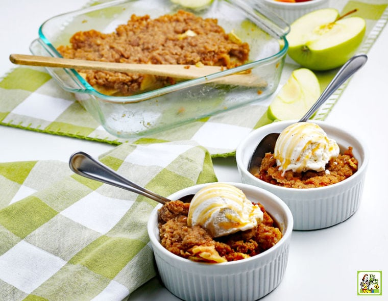 A baking dish of gluten free apple crisp, bowls with scoops of ice cream, slices of apples, and green and white napkins.