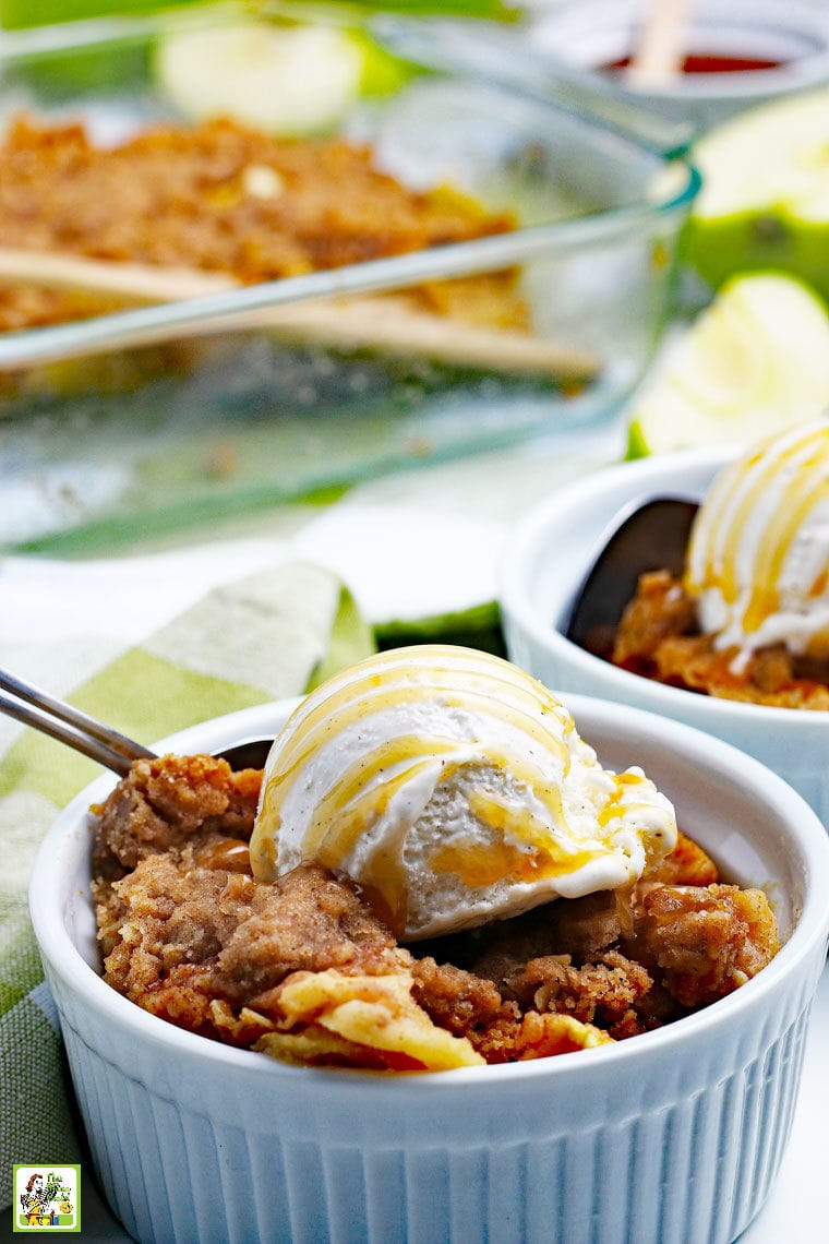 A white bowl of warm apple crisp with a scoop of vanilla ice cream drizzled with caramel sauce and a spoon.