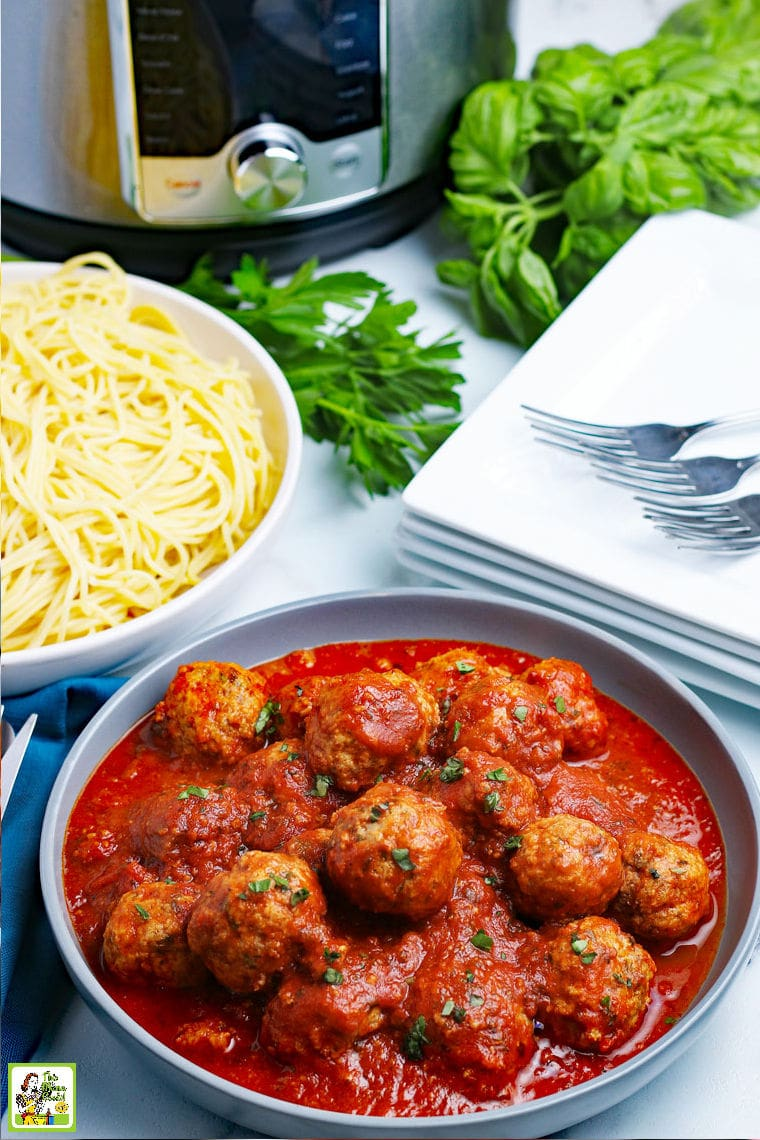 A bowl of pressure cooker meatballs in sauce with pasta, napkins, dishes and forks.