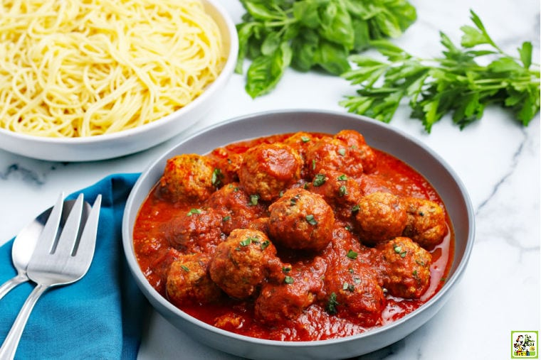 A large bowl of Instant Pot Meatballs in sauce, a large bowl of spaghetti, fresh sprigs of parsley and basil, serving utensils, and a blue cloth napkin.