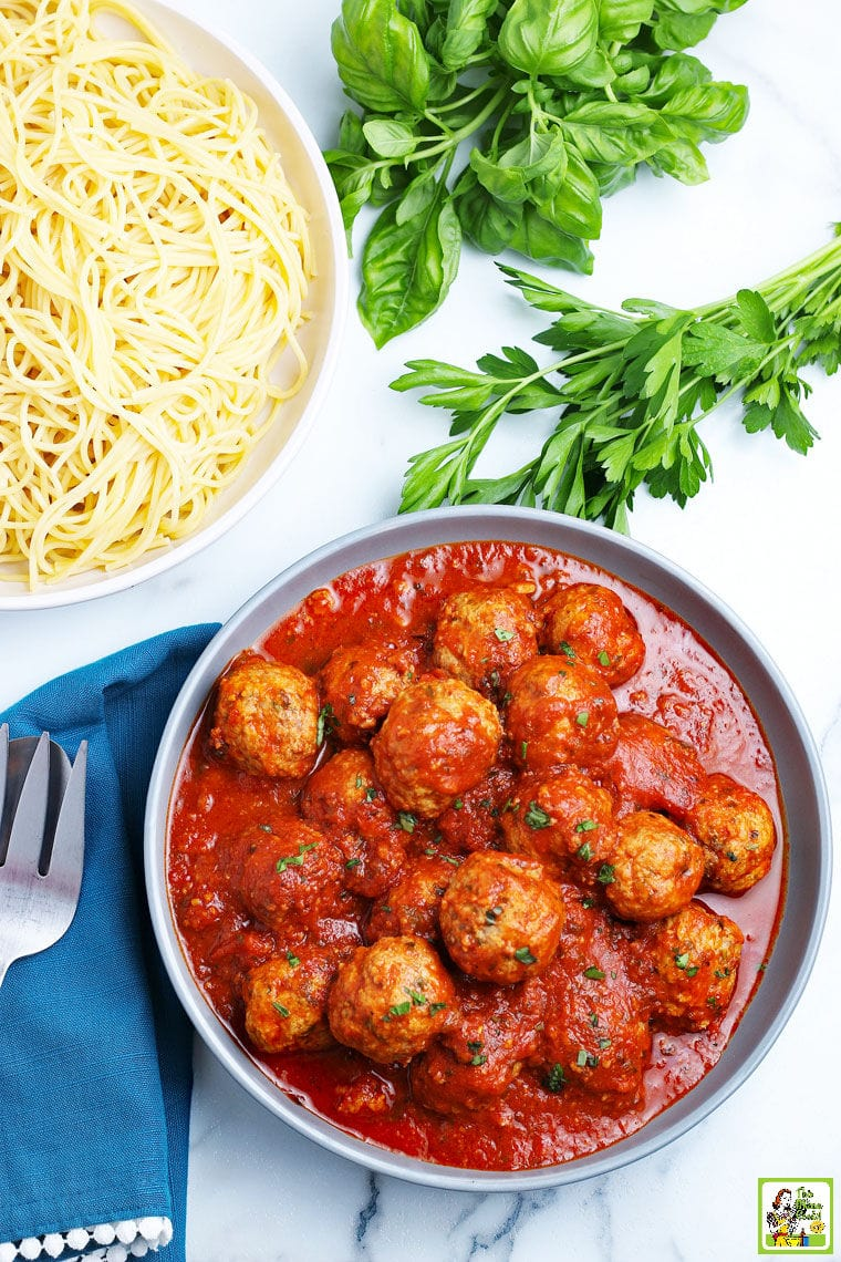 A bowl of Instant Pot Meatballs with spaghetti, parsley, basil, serving spoon and fork, and napkin.