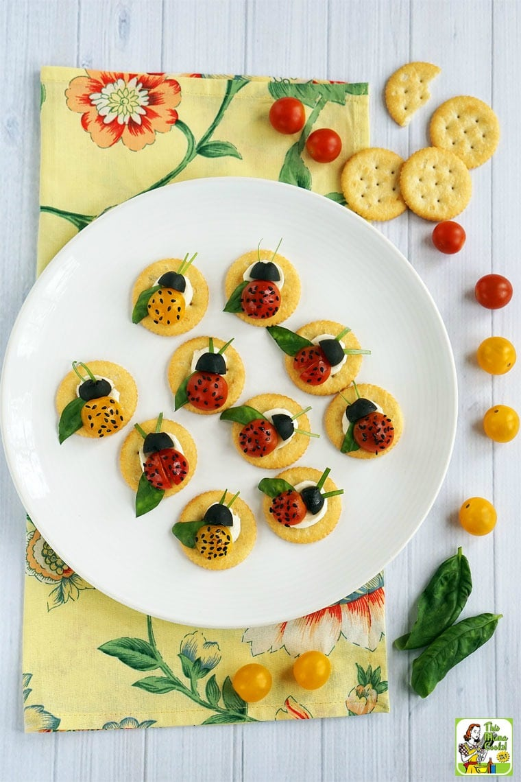 Caprese Ladybugs Appetizers on a white plate with crackers, tomatoes and basil with a floral napkin.