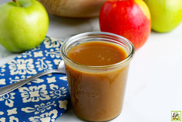 Vegan Caramel Sauce in a glass jar with a spoon, napkin, and apples.
