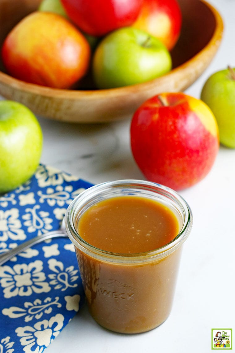 A glass jar of homemade vegan caramel sauce, a bowl of apples, a spoon, and a blue and white napkin.