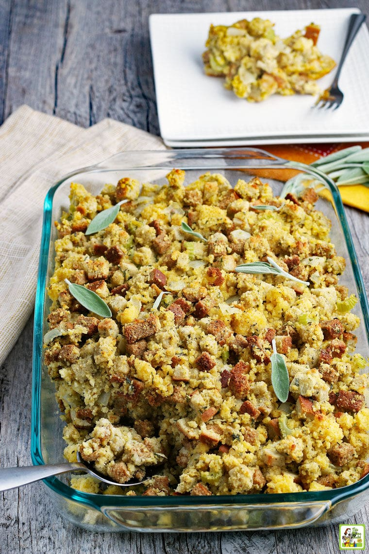 A glass pan of Cornbread Stuffing with plates and napkins.