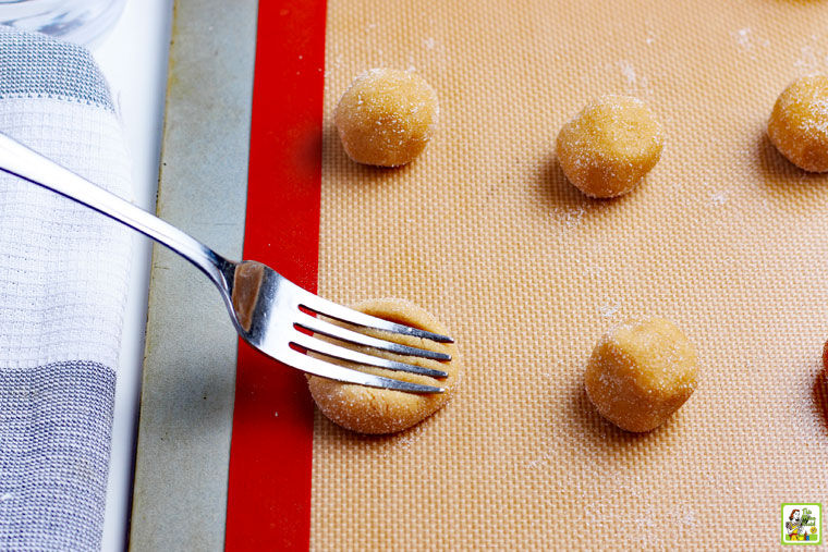 Flattening the cookie dough balls with a fork to make a criss-cross pattern.
