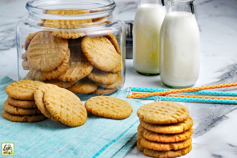 Stacks and a glass jar of Gluten Free Peanut Butter Cookies with jars of milk and colorful paper straws.