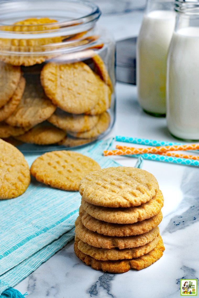 Stacks of peanut butter cookies with a glass jar of cookies and jars of milk.
