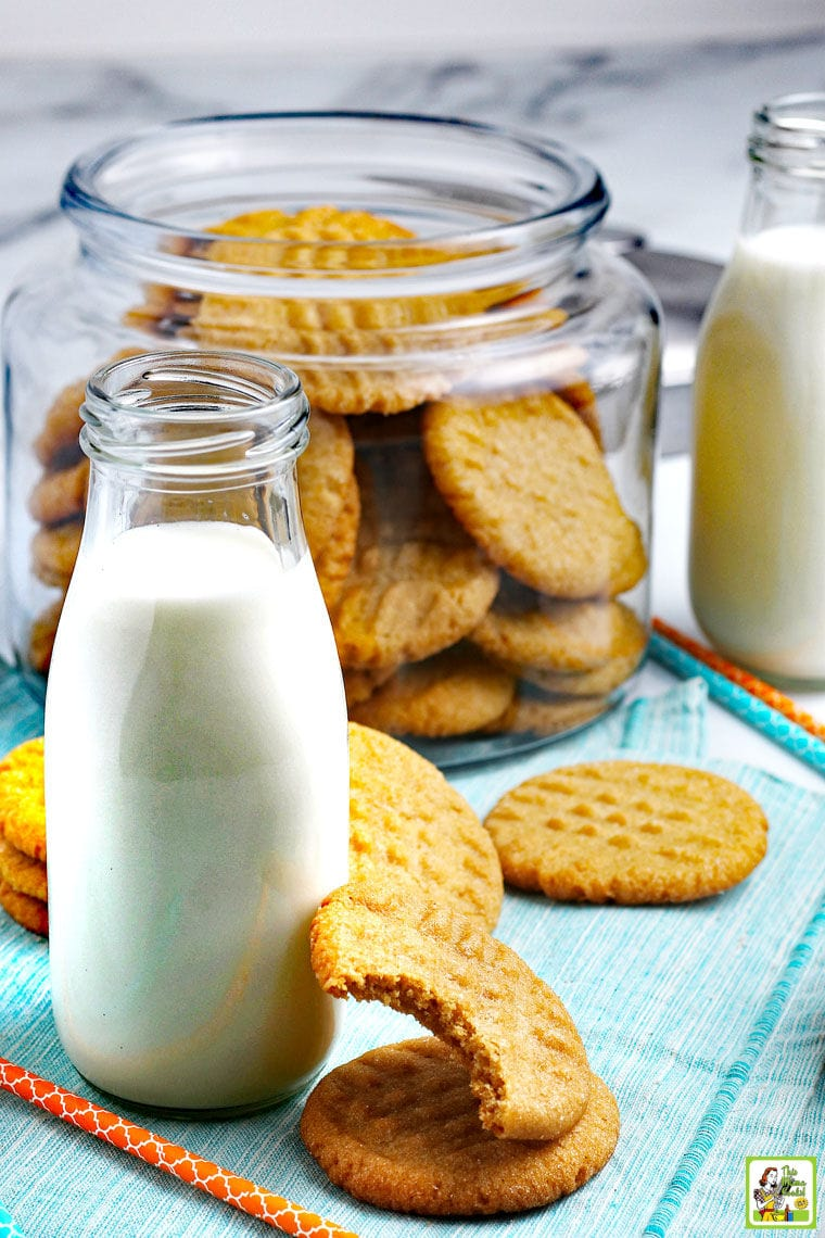 Peanut butter cookies with pint bottles of milk and a glass jar of cookies in the background.