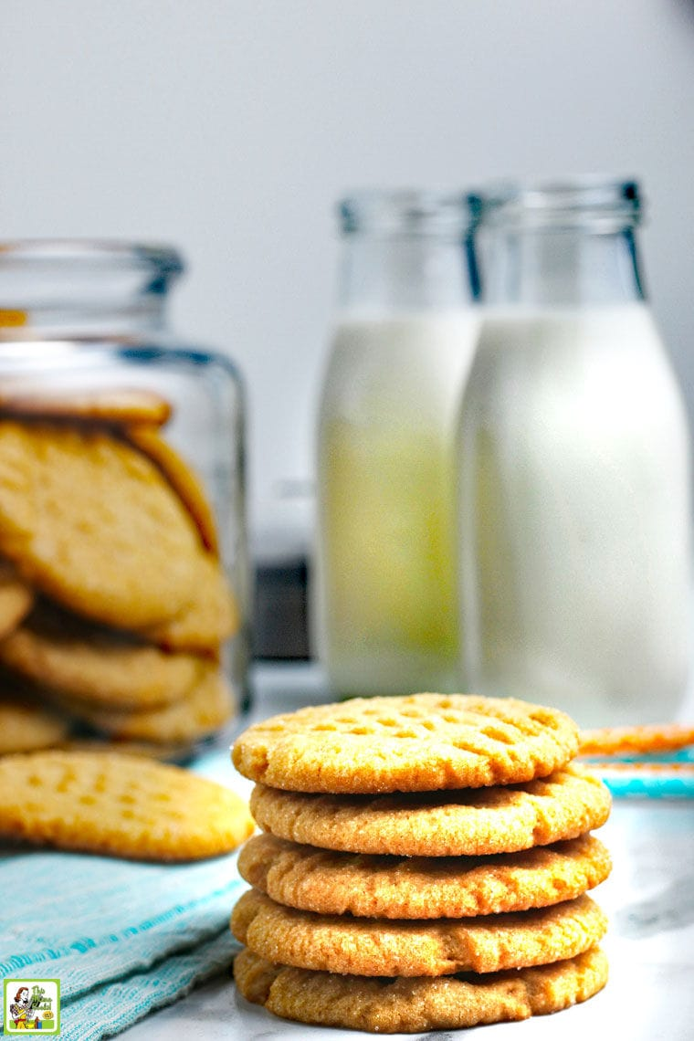 A stack of cookies with bottles of milk and a jar of cookies in the background.