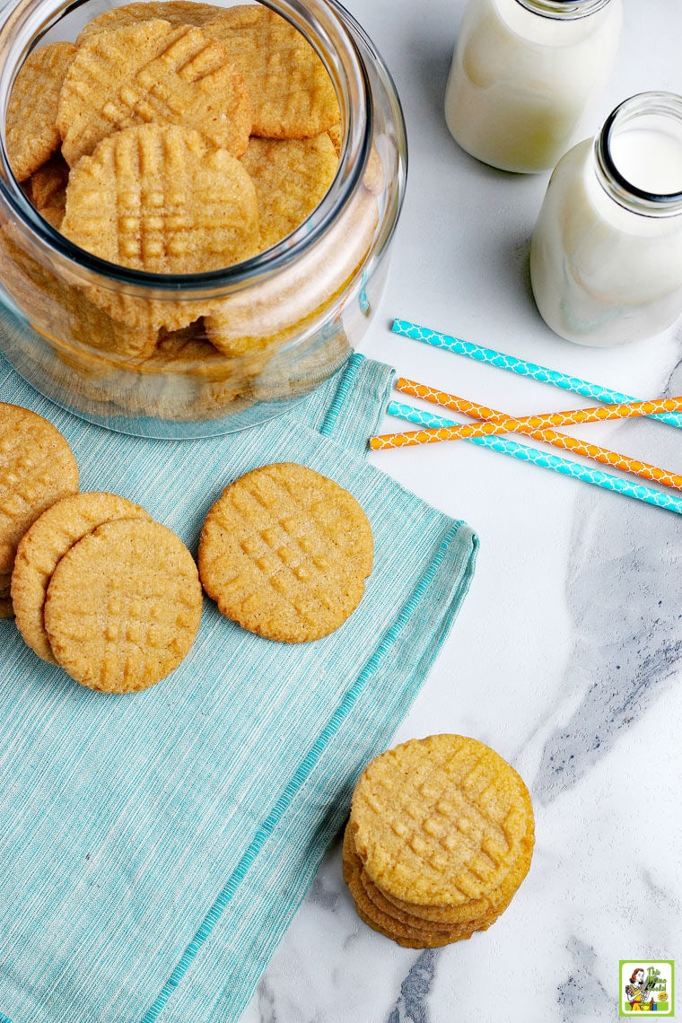 Overhead shot of peanut butter cookies on a blue napkin with a jar of cookies , blue and orange paper straws, and milk bottles.